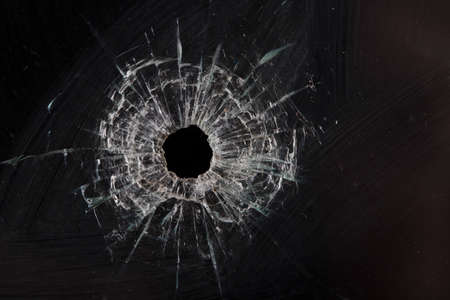 bullet holes in glass isolated on black Stock Photo - 36621387