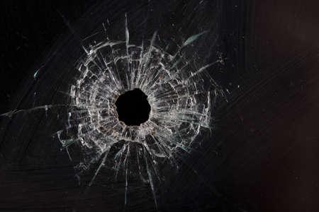 gunshot: bullet holes in glass isolated on black