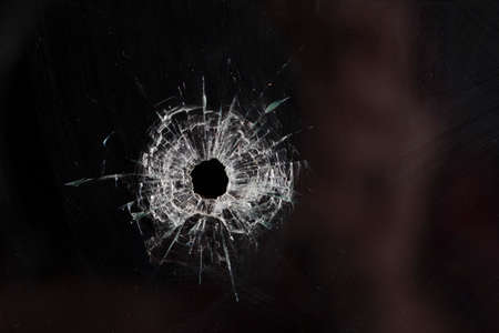 bullet holes in glass isolated on black Imagens - 36115180