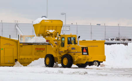 cleaning crew: JFK Airport January 2011 Wheel loader machine unloading snow to snow melter with airport work crews after large storm at JFK Airport on January 13, 2011 clearing off taxi ways and run ways.