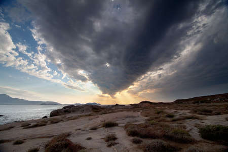 dramatic sunset with clouds, over a rocky coast Stock Photo