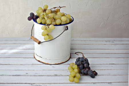 grapes in an old metal bucket over a wood table