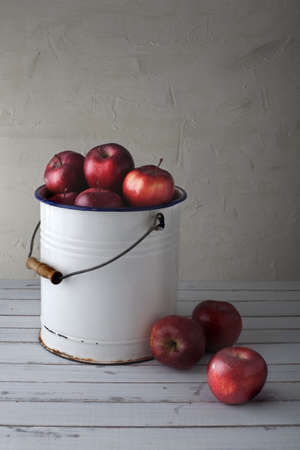 stark: red apples in an old iron bucket, focus is on the lower right apple