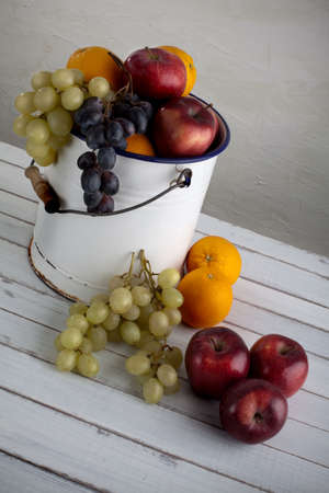 a fruit still life composition with grapes, apples, and oranges in a very old metal bucket