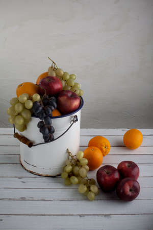 vertical composition: a fruit still life composition with grapes, apples, and oranges in a very old metal bucket