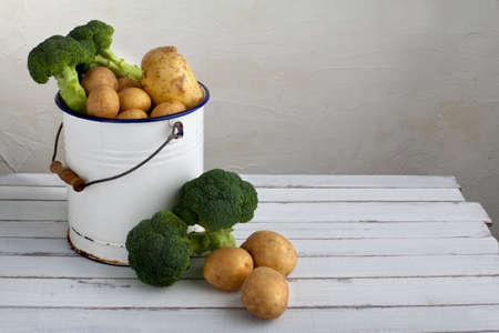 potatoes and broccoli in an old iron bucket on a wood table