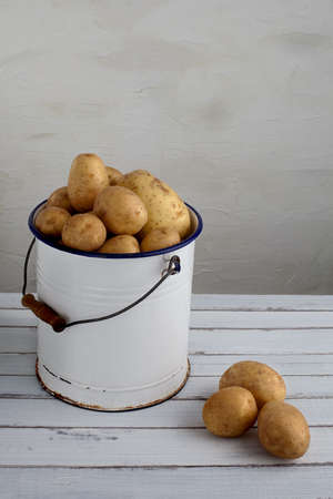 potatoes in an old iron bucket on a wood table