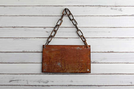 a rusted iron signboard, hang on a wood wall