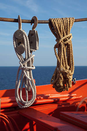 nautical ropes knots on a red wooden boat Stock Photo