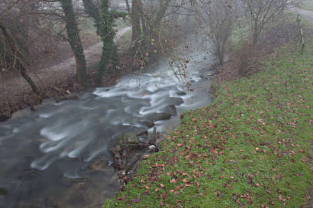 Water flow of a small river, slow shutter timing, in winter.
