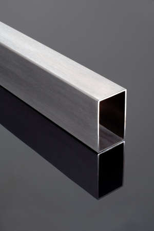 stainless steel square pipe, on a black glossy surface Stock Photo