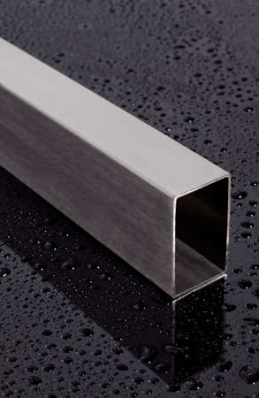stainless steel square pipe, on a black surface with water drops