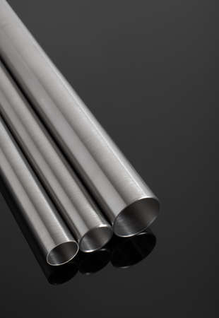 three stainless steel pipes, on a glossy black surface,  vertical composition