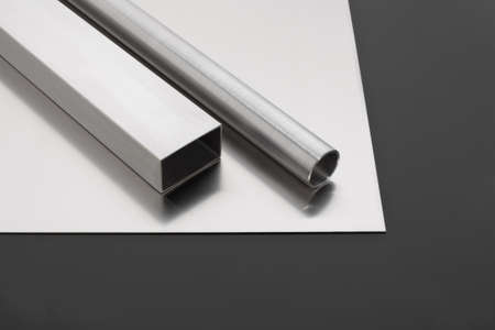 stainless steel sheet: Stainless steel pipes and sheet on a black surface Stock Photo
