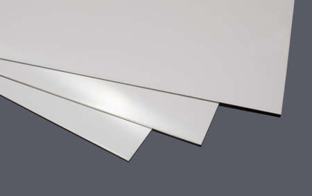 stainless: three stainless steel sheets, on a black surface Stock Photo