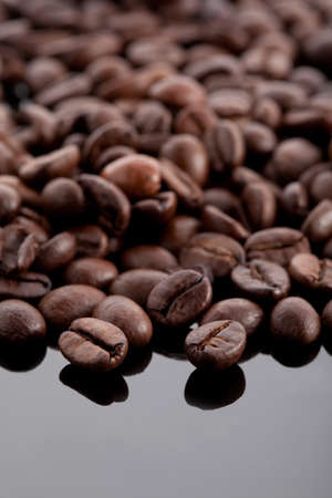 coffee beans on black glossy background reflected in it