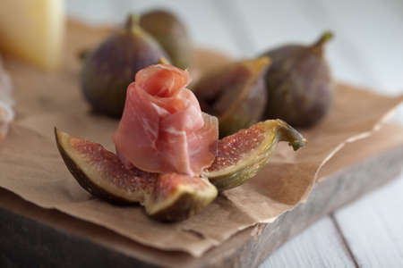 fig and ham on a white rustic table Stock Photo