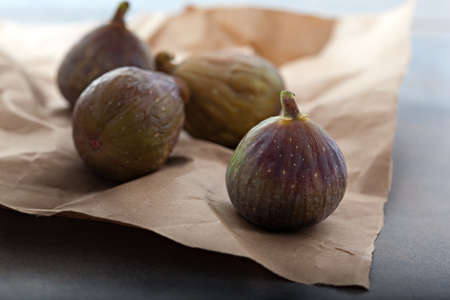 purple fig: bunch of fig, seasonal fresh fruit on a rustic brown paper Stock Photo