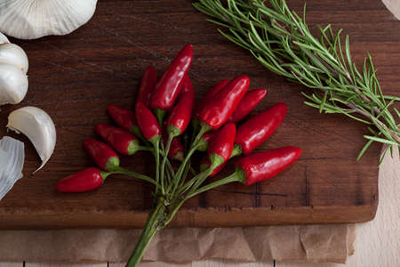 hot pepper, garlic, rosemary on a chopping board
