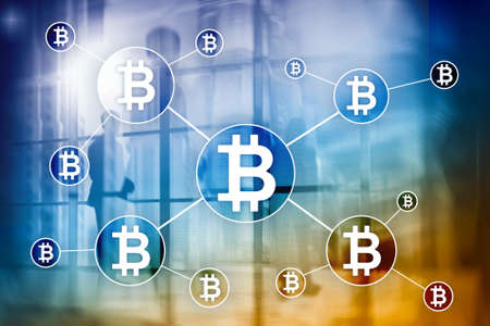 Bitcoin cryptocurrency and blockchain technology concept on blurred skyscrapers background.