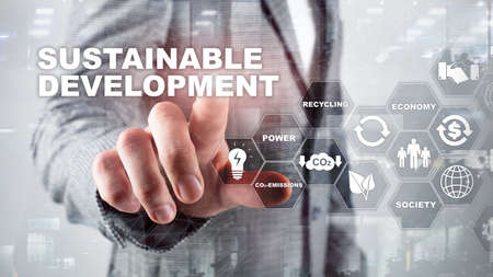Sustainable development, ecology and environment protection concept. Renewable energy and natural resources. Double exposure of success businessman with abstract building. Imagens