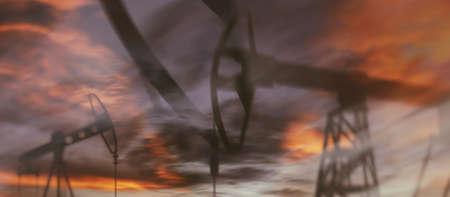 Oil derricks against the sky. Oil rig pump double exposure. Standard-Bild