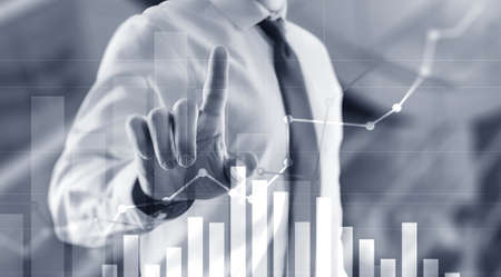 Businessman drawing graph with marker on media screen Banco de Imagens