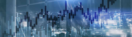 Candles and stock market charts on abstract background. Silhouettes and modern city.
