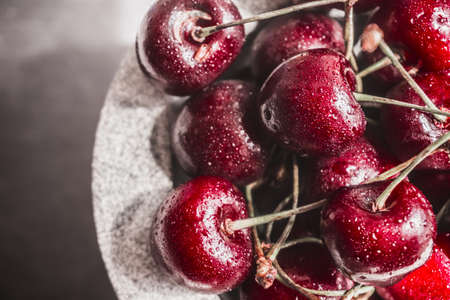Red cherries with waterdrops in the stone bowl