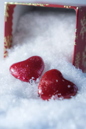 Valentines day red hearts with the gift box on the snow