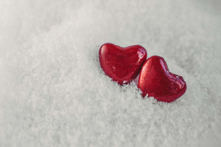 Valentines day; Two red hearts on othe snow. Holidays card