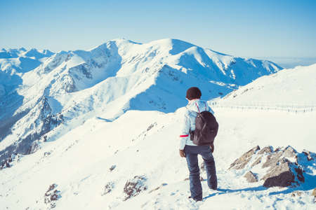 Woman hiker, healthy lifestyle. Trekking and hiking on snow white winter nature, beautiful inspirational mountain landscape. Stock Photo