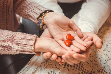 Couple colding two hearts in their hands; couple in love; Valentines Day background Stock Photo