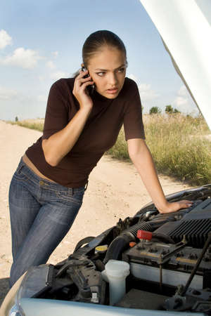 bonnet up: Young woman stands next to the car with bonnet up and calls for help.