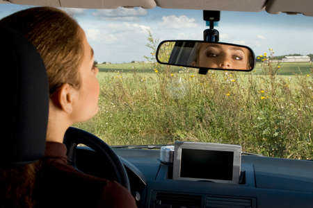 drivers seat: Young woman sits on drivers seat and Looks in the rear-view mirror. Stock Photo