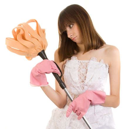 domestic staff: Displeased bride in washing up gloves with broom, isolated on white background.
