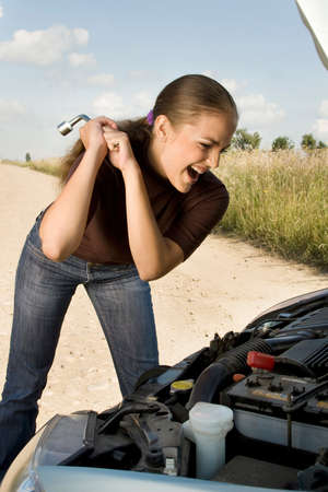 threaten: Furious young woman threaten with lug wrench at the car engine.