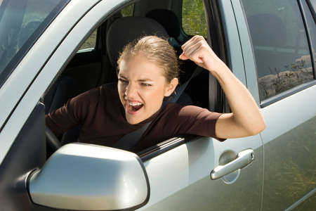 shaking out: Young woman driver yelling and  shaking her fist out car window. Stock Photo