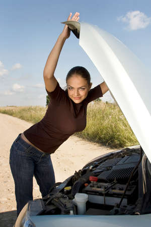 bonnet up: Young attractive woman stands next to the car with bonnet up Stock Photo