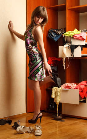 Beautiful young woman stands near her wardrobe  on high heels