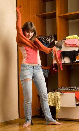 Beautiful young woman stands near her wardrobe and puts on  sweater Stock Photo - 48965056