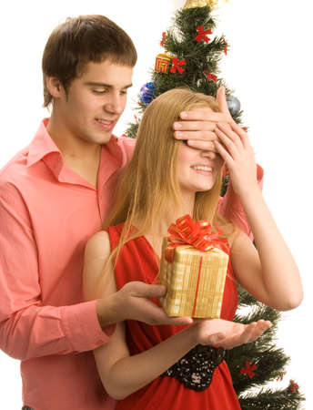 closing eyes: Guy is closing eyes of the girl and giving her a present, isolated on white background Stock Photo
