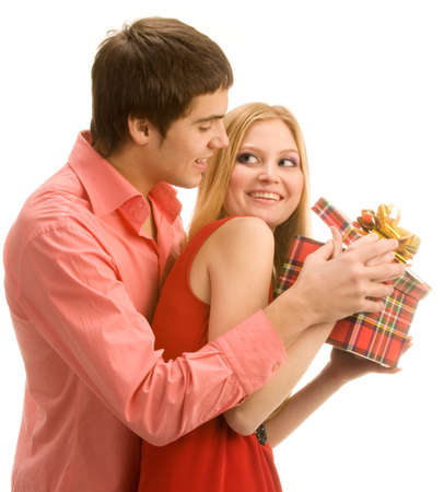 loving couples: Guy is trying to look into girls gift box, isolated on white background