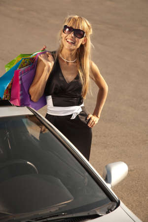 personal shopper: Girl with shopping bags stands near  her car