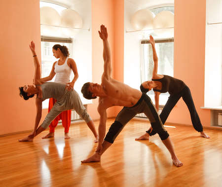 yoga class: Yoga group practicing under instructors guidance
