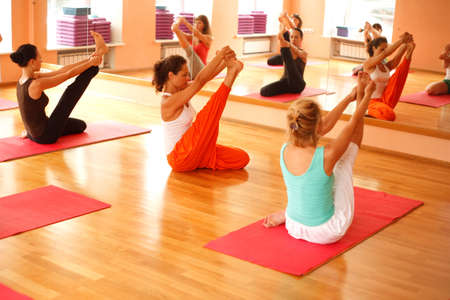 yoga class: Women practicing yoga at health club Stock Photo