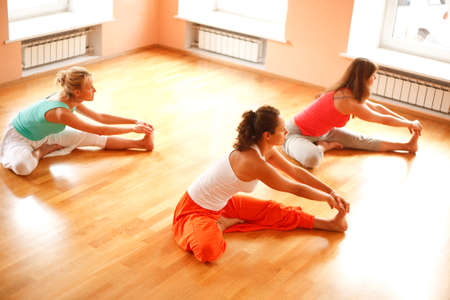 yoga pose: Three women is doing yoga at health club.High angle view