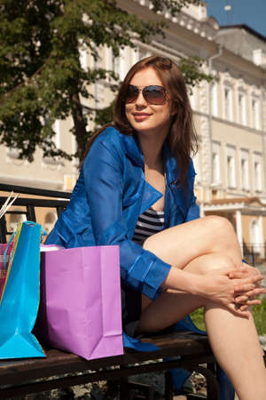 personal shopper: Cheerful young woman is sitting on the bench with shopping bags Stock Photo