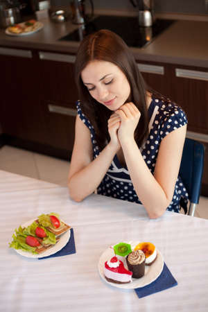 fancy cakes: Young woman at her kitchen and choosing between diet sandwiches and fancy cakes