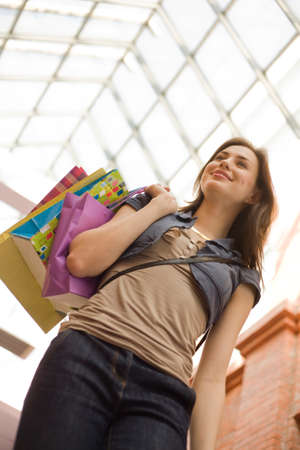 personal shopper: Young woman at shopping mall with shopping bags,low angle view Stock Photo